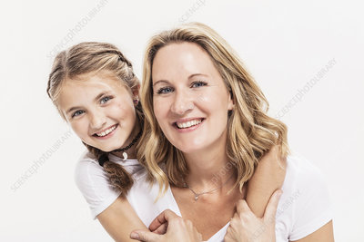 Studio portrait of girl with arms around her mother
