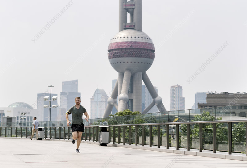 Young male runner in Shanghai financial centre, China