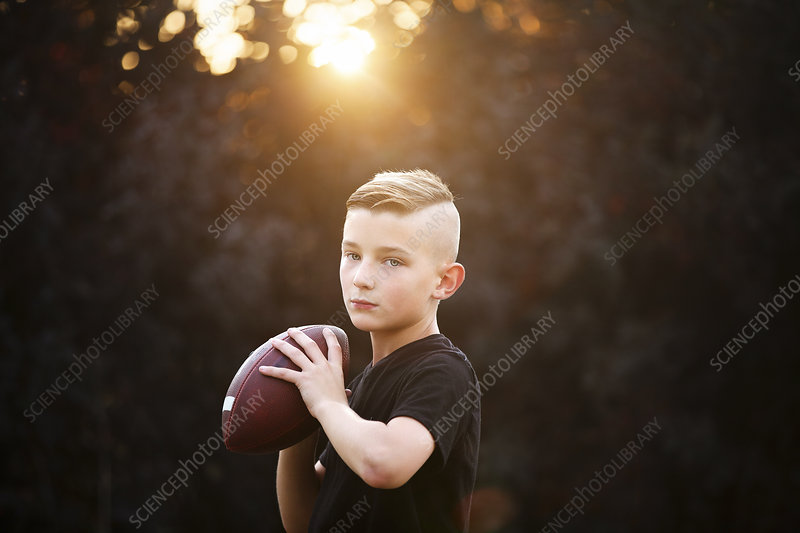 Boy practicing american football in garden