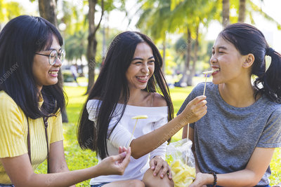 Friends enjoying snacks in park, Bangkok, Thailand