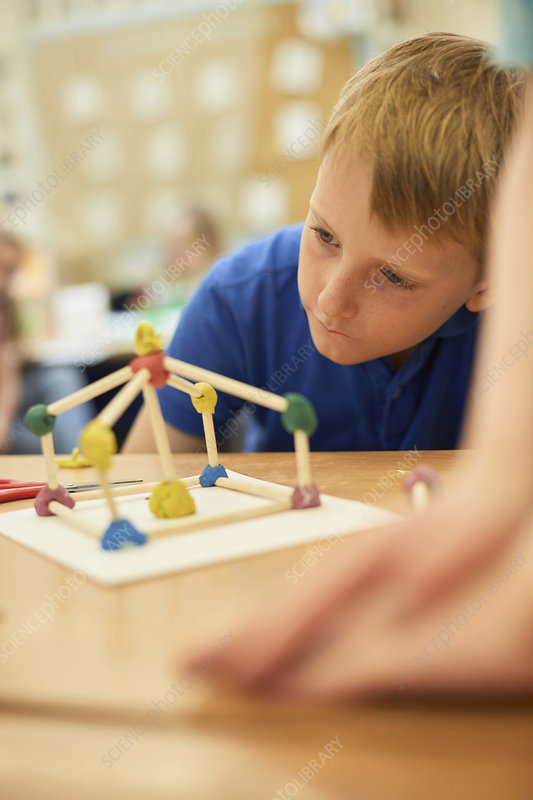 Primary schoolboy looking at plastic straw model