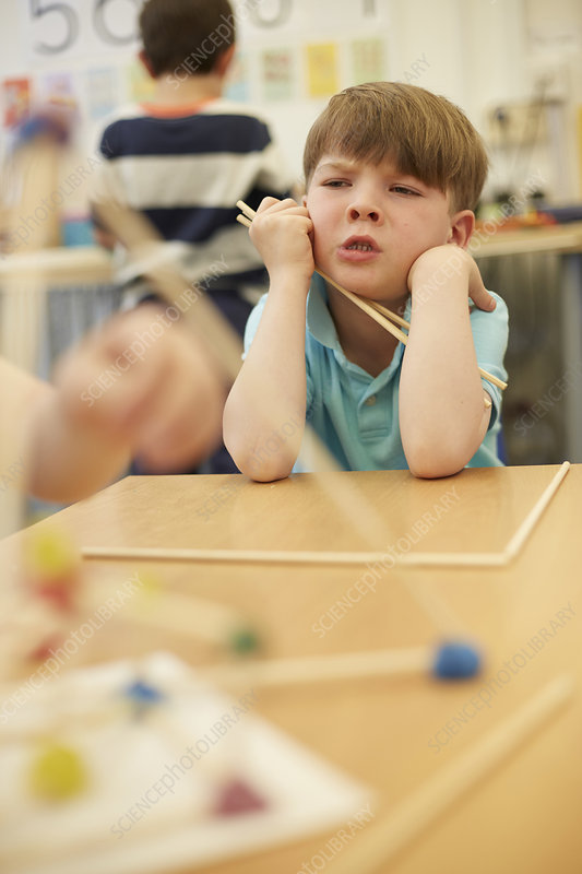 Primary schoolboy with plastic straws on classroom desks