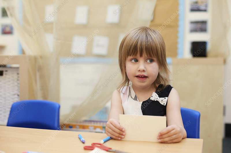 Primary schoolgirl looking sideways from classroom desk