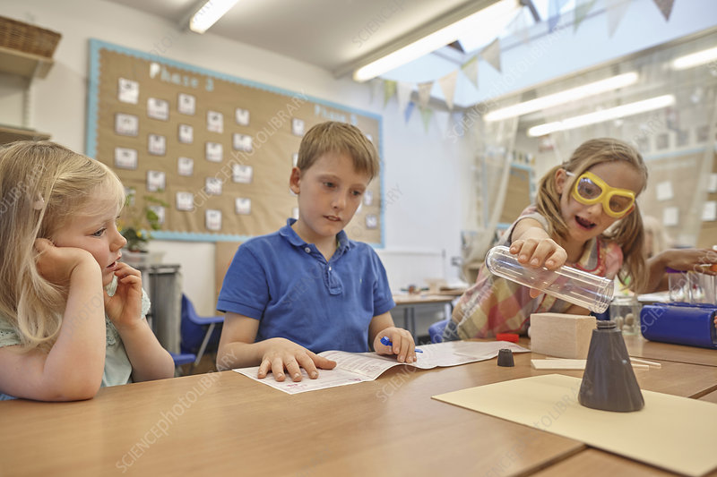 Primary schoolgirls and boy doing experiment