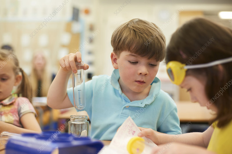 Primary schoolboy and girls doing test tube experiment
