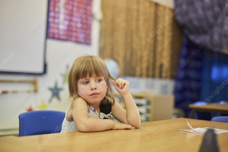 Primary schoolgirl fiddling with hair at classroom desk
