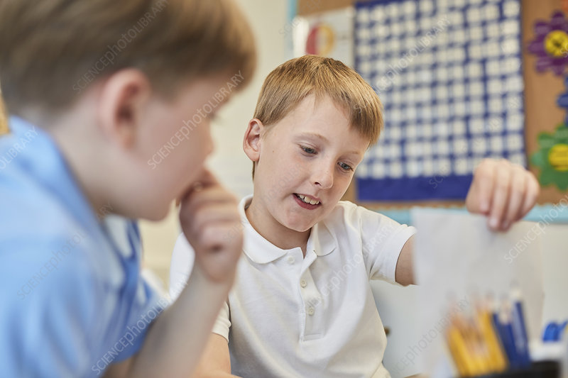 Schoolboys learning together in classroom lesson