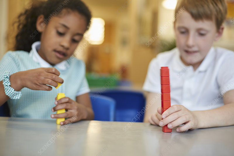 Schoolboy and girl stacking toy blocks in classroom