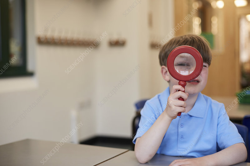 Schoolboy looking through magnifying glass, portrait