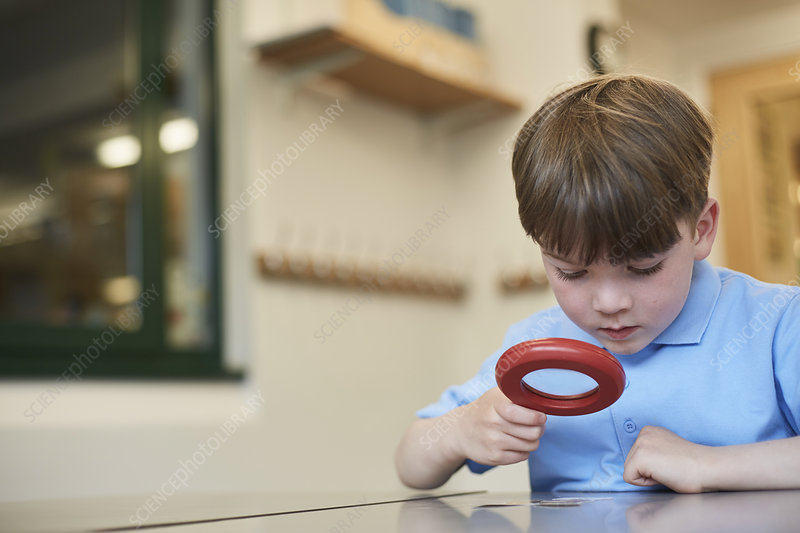 Schoolboy looking through magnifying glass lesson