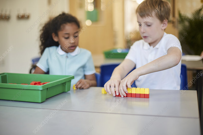Schoolboy and girl constructing toy blocks in classroom