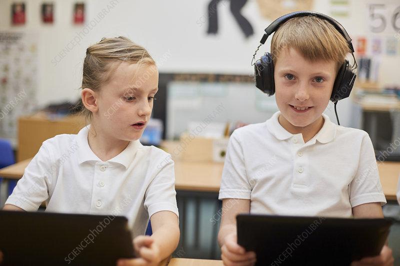 Schoolboy listening to headphones in class, portrait