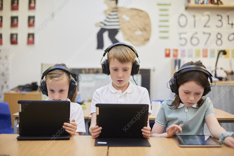 Schoolboy and girls listening to headphones in class