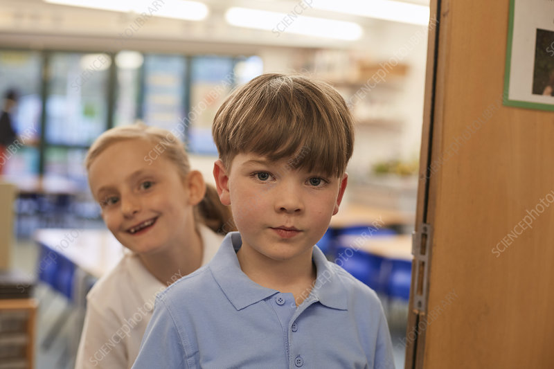 Portrait of schoolboy and girl in classroom