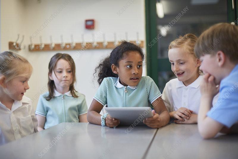 Schoolgirls and boy using digital tablet