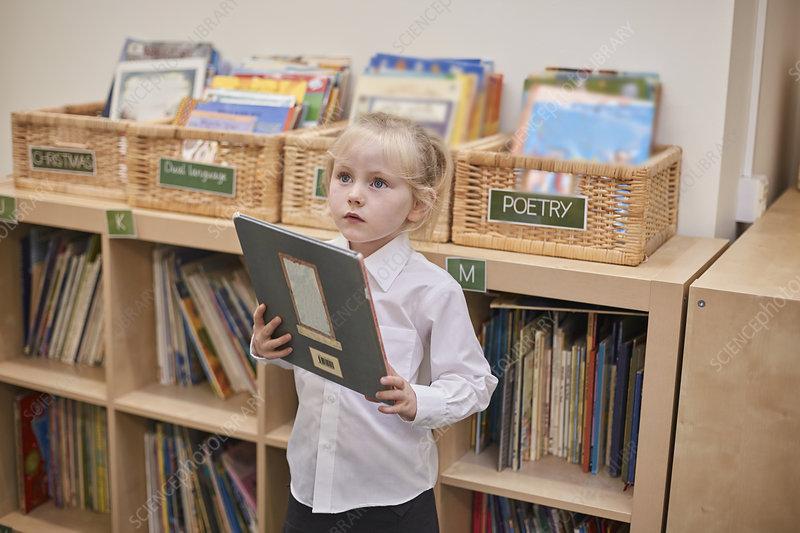 Cute schoolgirl holding book in classroom