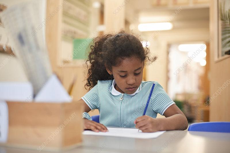 Schoolgirl writing at classroom desk in primary school