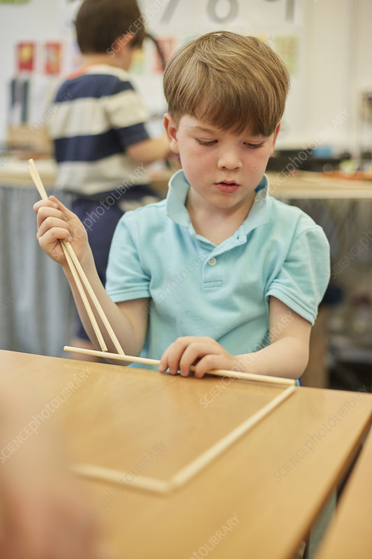 Schoolboy making ball and stick model in classroom