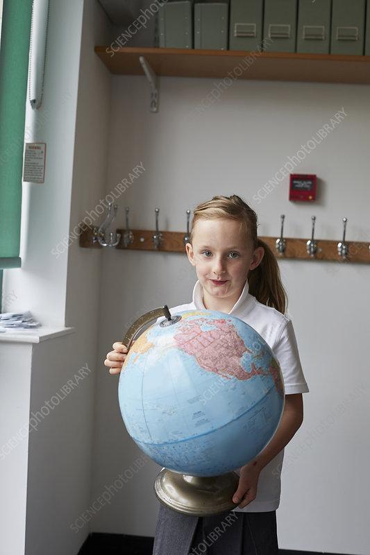 Schoolgirl holding globe in classroom, portrait