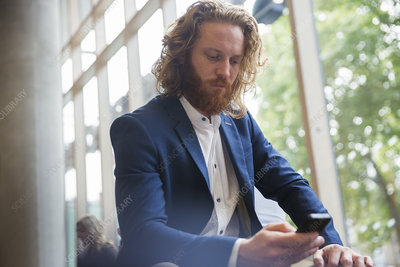 Businessman texting with smart phone