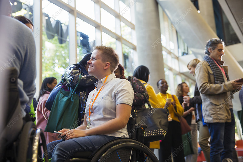 Smiling woman in wheelchair at conference