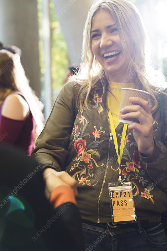 Smiling woman with coffee at conference