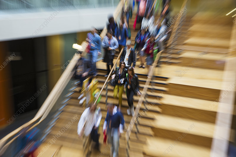 Blurred motion people descending wooden stairs