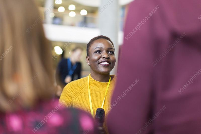 Smiling female speaker talking to audience