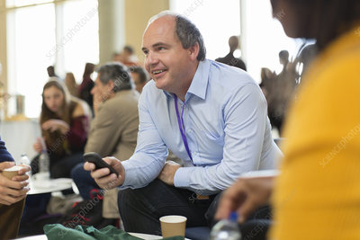 Smiling businessman using smart phone at conference