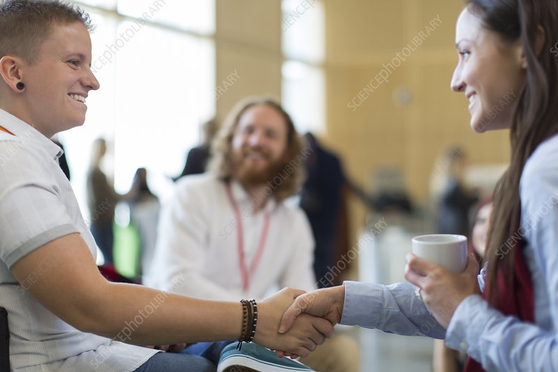 Businesswomen shaking hands at conference