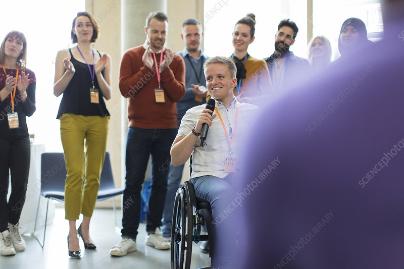 Audience clapping for female speaker in wheelchair