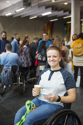 Woman in wheelchair drinking coffee at conference