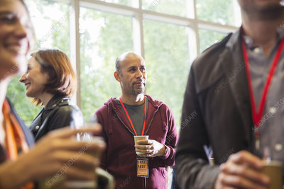 Businessman drinking coffee, networking at conference