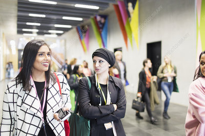 Businesswomen walking and talking at conference
