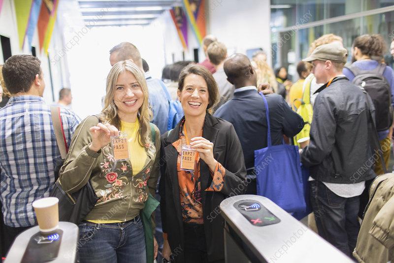 Portrait women showing lanyard conference passes
