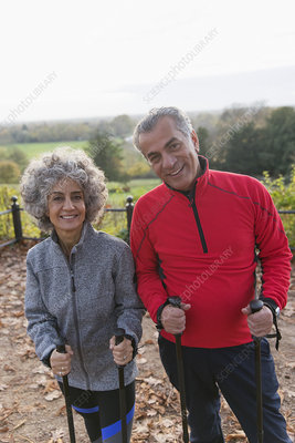 Portrait smiling, active senior hikers with poles