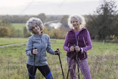 Portrait active senior women hikers with poles
