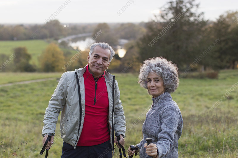 Portrait active senior couple hiking in rural field
