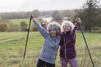Senior women friends hiking with poles