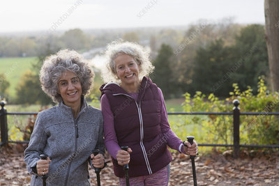 Portrait active senior women friends hiking with poles