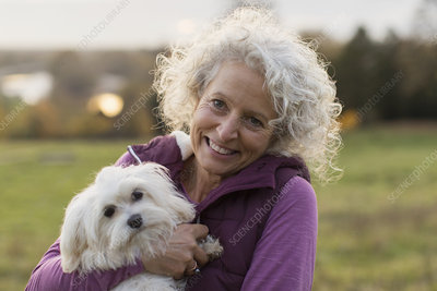Portrait smiling, happy active senior woman holding dog