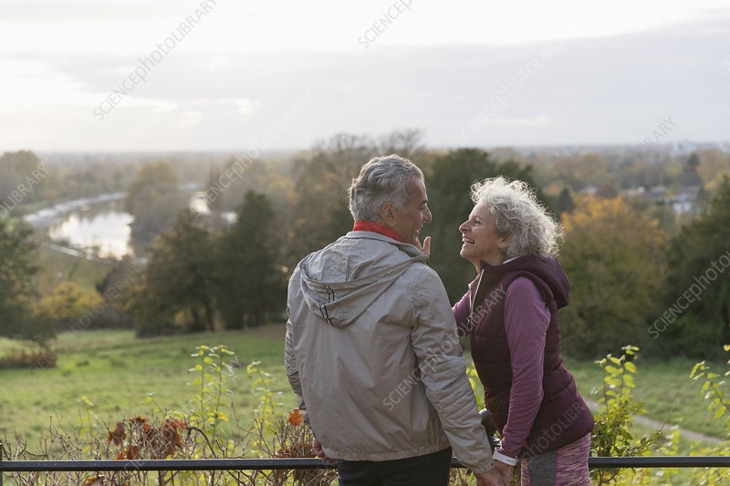 affectionate active senior couple in autumn park