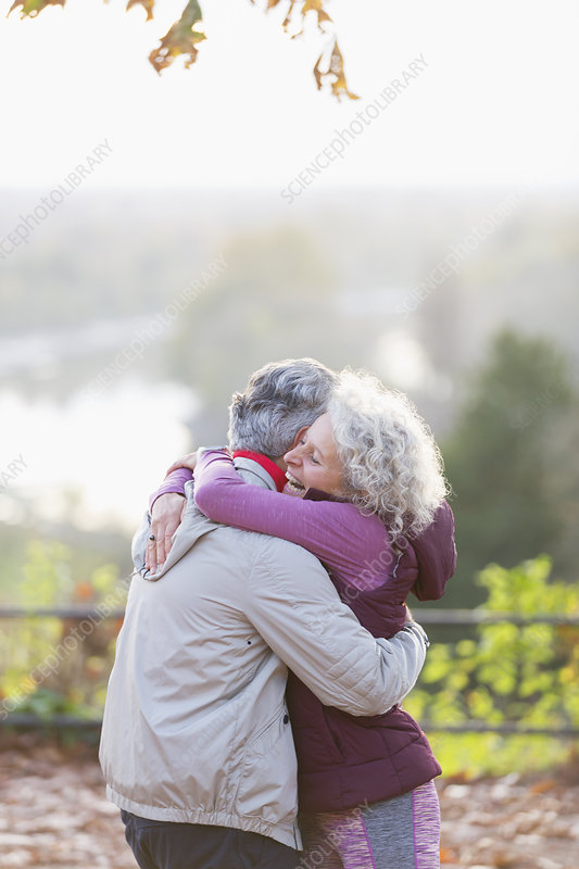 Affectionate active senior couple hugging in park