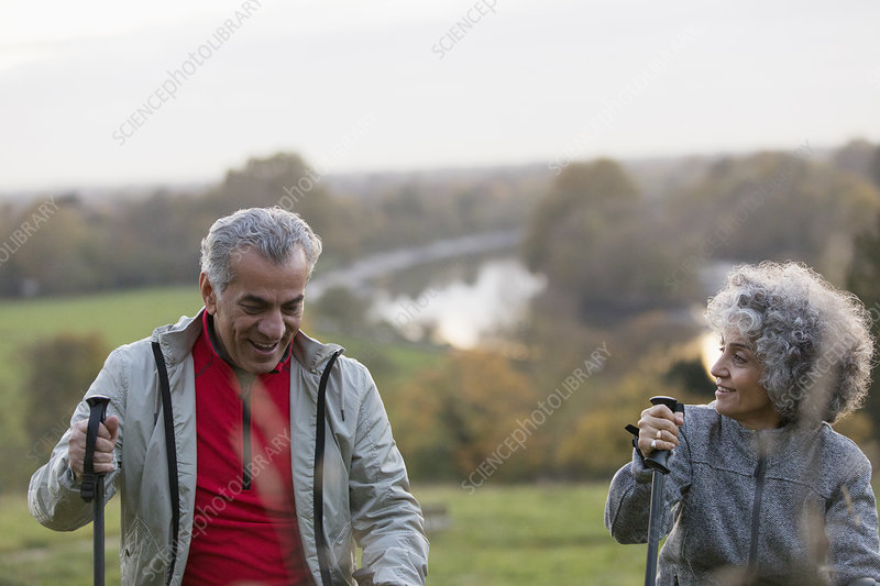 Active senior couple hiking with poles in park