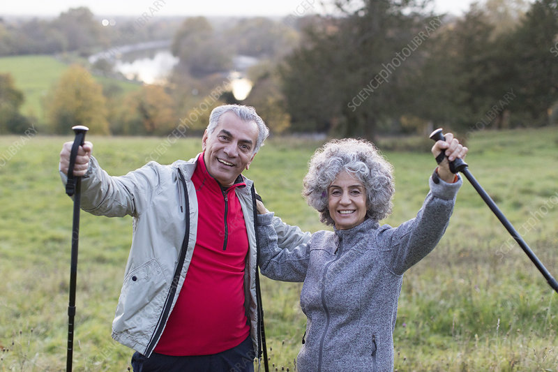 Portrait enthusiastic, senior couple hiking with poles