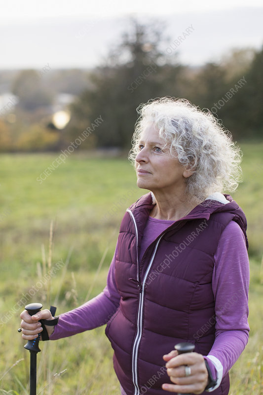 Thoughtful active senior woman hiking with poles