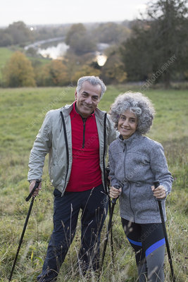 Portrait active senior couple hiking with poles