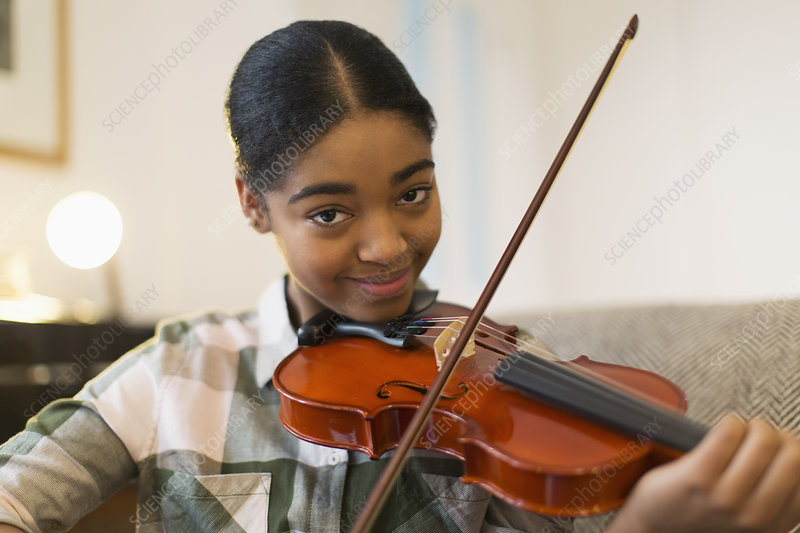 Portrait confident teenage girl playing violin