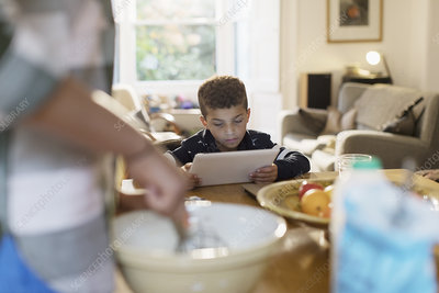 Curious boy using digital tablet in kitchen