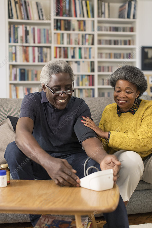 Senior couple checking blood pressure in living room
